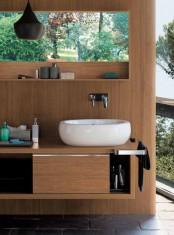 a contemporary bathroom with a wooden wall, a matching storage unit, a sink, a pendant lamp and a gorgeous view is a chic idea