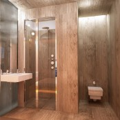 a contemporary bathroom fully clad with stained wood, with a shower enclosed in glass and wood, with a wall-mounted sink and a modern toilet
