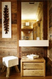 a contemporary bathroom clad with wood, with a mirror in a wooden frame, a wall-mounted sink, a wooden storage unit and a cool cube stool