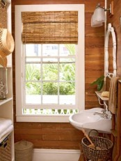 a small rustic bathroom fully clad with wood, with a window with shades, a sink, some baskets for storage and a large storage unit