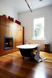 a modern bathroom with a wooden floor, a wooden storage unit that includes a fireplace, monograms and a black vintage bathtub