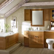 a modern rustic bathroom with wooden storage cabinets, white countertops and a sink, a bathtub clad with wood and wooden beams on the ceiling