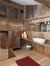a bathroom fully clad with rough wood, with pendant lamps and an oval sink is a stylish space to be