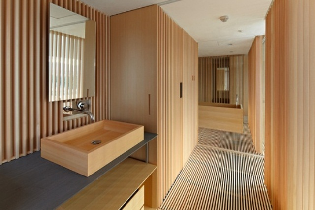 a minimalist light stained wooden bathroom with a wood slab wall and floor, with large storage units and a wooden bathtub