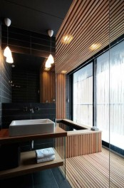 a minimalist bathroom done with light stained wooden slab and black skinny tiles, with pendant lamps and a large window for more light