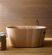 a neutral minimalist bathroom fully clad with light-stained wooden slabs, a wooden bathtub and a matching stool is very zen-like
