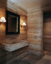 a rustic bathroom clad with light stained wood and with tiles on the floor, with a wall-mounted stone sink and sconces