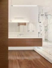 a contemporary bathroom with a wooden floor, a white marble shower space, a wooden vanity and a large mirror is bold and cool