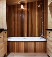 a modern bathroom with a bold reclaimed wood wall and a bathtub, with neutral stained vanities is cozy and welcoming