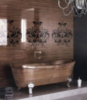 a refined bathroom with a stained wood wall with stencils and a wooden bathtub, a crystal chandelier and dark towels is bold and cool
