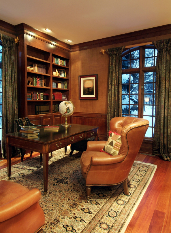 a vintage home office with rich stained furniture, leather chairs, printed curtains, a rug and fabric covered walls