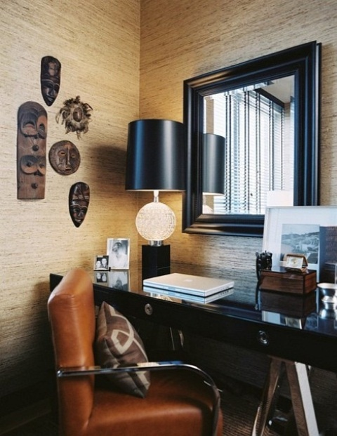 a refined home office with a black desk and a mirror in a black frame, masks for decor and an amber leather chair