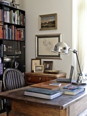 an eclectic home office with a modern bookcase, a rich stained desk, artworks and elegant metal lamps