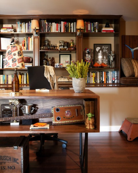 a mid-century modern home office with rich stained wooden furniture, a desk with storage, lamps and potted greenery