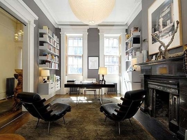 a stylish home office with grey walls, a white shelving unit, a fireplace and black leather chairs