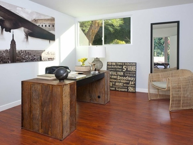 a unique home office with a reclaimed wood desk, a rattan chair and lots of unusual artworks