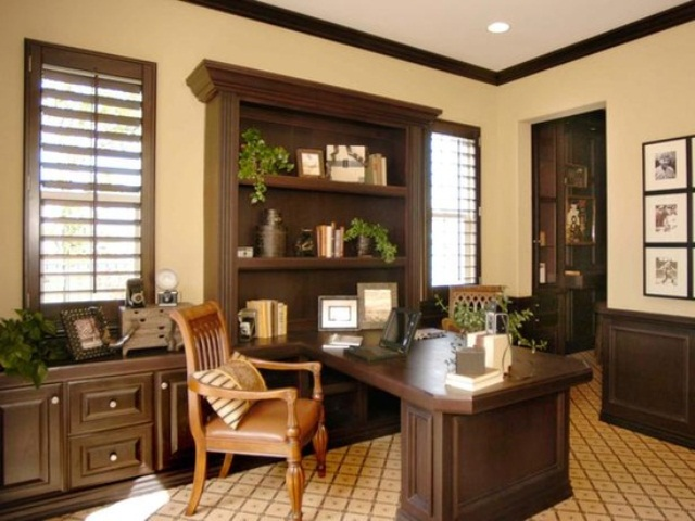 a vintage inspired sandy and dark chocolate home office with stylish furniture, an amber leather chair and potted greenery