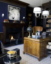 an elegant vintage-inspired masculine home office with navy walls, dark bookcases, a light stained desk and a leather chair