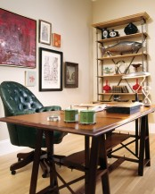 an eclectic home office with a wooden trestle desk, a metal and wood shelving unit and a gallery wall