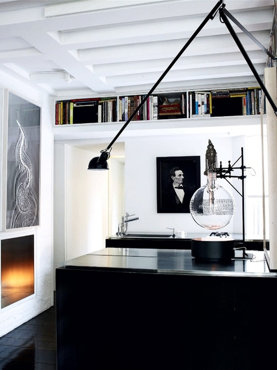 a minimalist monochromatic home office with a black desk, an open bookshelf, a fireplace and lots of artworks