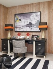 a bright home office with a wood statement wall, a black desk and a striped rug plus table lamps with bright accents