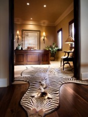 a luxurious home office with neutral walls, a refined desk, a faux animal skin and elegant lamps