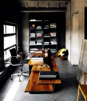 a moody home office with concrete walls and a floor, a black bookcase, a wooden desk with various levels plsu a leather chair