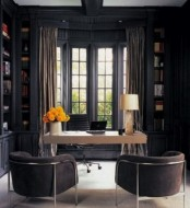 a moody home office with graphite grey walls and built-in bookcases, a white desk and comfy upholstered chairs