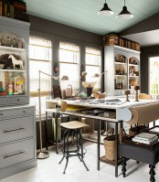 an eclectic home office done in neutrals, a tall desk, bookcases and a black ottoman