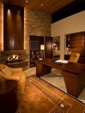 an elegant home office with a faux stone wall, rich stained wooden furniture and a fireplace, a rug and leather chairs