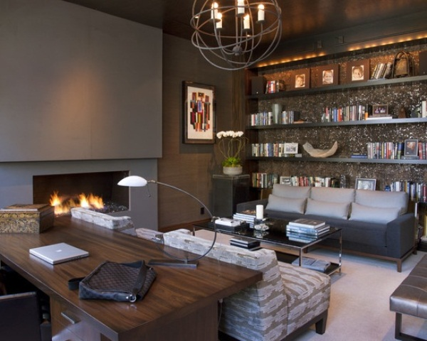 a moody home office with a concrete fireplace, a shiny wlal with open shelves, a rich stained wooden desk, catchy lamps and upholstered furniture
