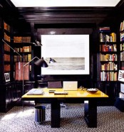 an elegant moody home office with black walls and built-in bookcases, a black and gold desk plus a mosaic floor