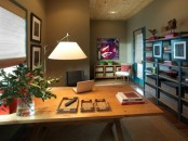 a cozy home office with a large open shelving unit, a wooden deks, a gallery wall and some bright artworks