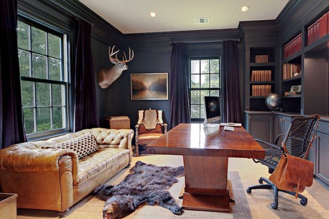 a refined moody home office with black walls, built in shelves, rich stained wooden furniture and a matching leather sofa