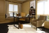 a modern home office done in tan and earthy shades, built-in furniture, a black desk and a chair plus artworks