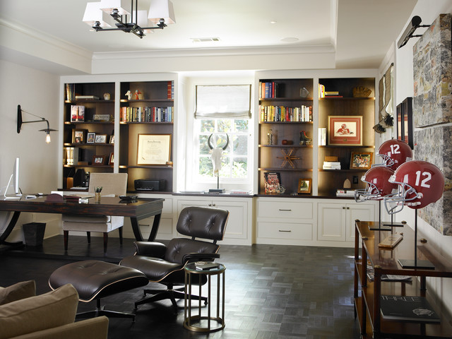 a stylish modern meets contemporary home office with built in shelves with lights, a dark desk and a leather chair plus a stand with helmets