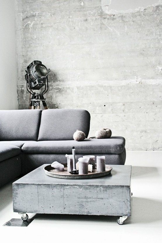 concrete walls echo with a concrete coffee table with casters, and a vintage floor lamp helps creating an industrial feel