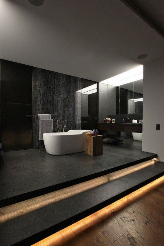 a minimalist moody bathroom with dark walls, a black floor, built-in lights, a stone accent walls, white appliances and a dark floating vanity