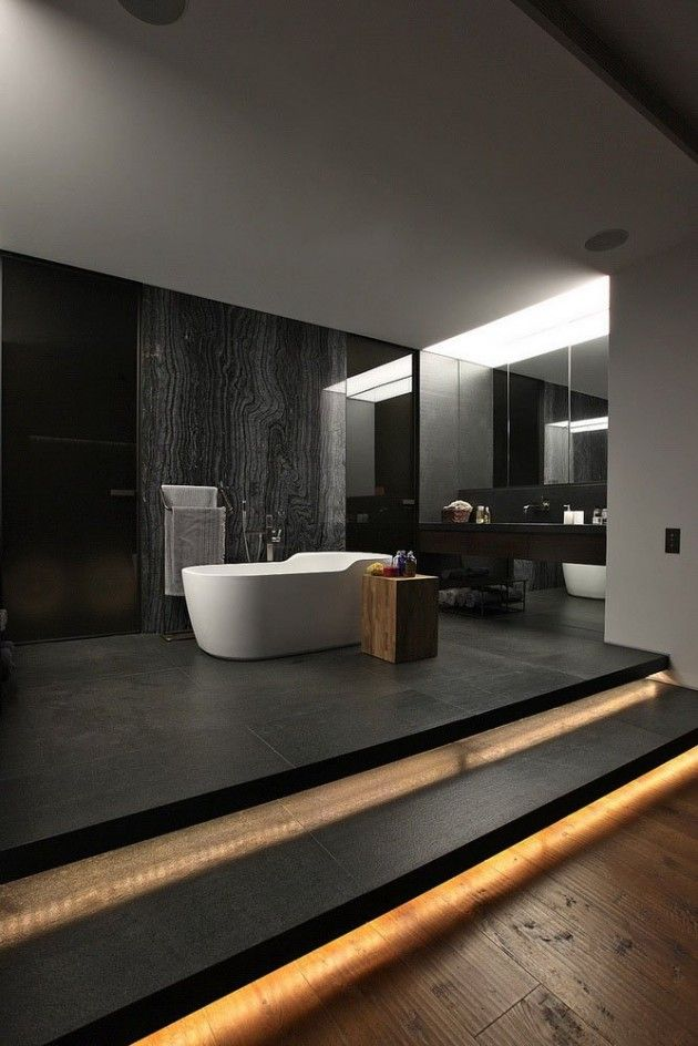 a minimalist moody bathroom with dark walls, a black floor, built in lights, a stone accent walls, white appliances and a dark floating vanity