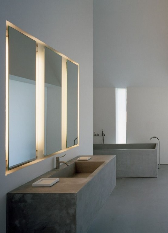 an ultra-minimalist concrete bathroom with a concrete bathtub and a floating vanity with a built-in sink plus mirrors with built-in lights