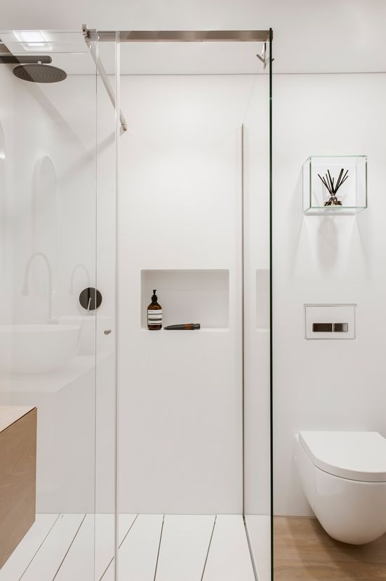 a small white minimalist bathroom with sleek walls, a wooden floor and vanity, built-in storage and white appliances