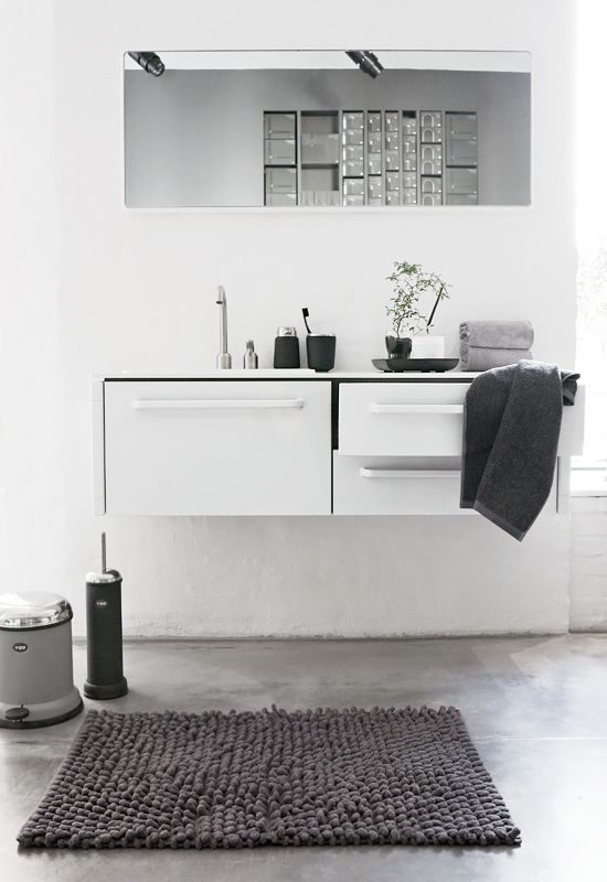 a minimalist neutral bathroom with a floating vanity with storage, a long mirror, grey linens and simple decor