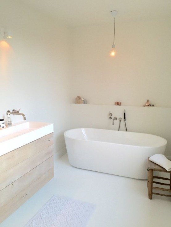 a white minimalist bathroom with sleek walls, a wooden floating vanity, white appliances, simple lights and accessories