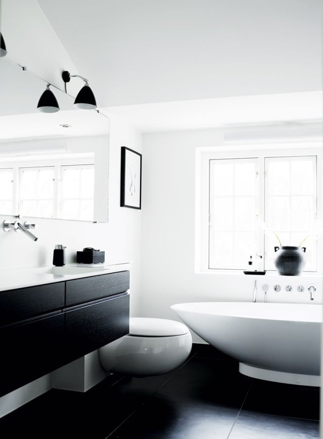 a minimalist contrasting bathroom with white walls, a black floor, a window, a black floating vanity and sconces and white appliances