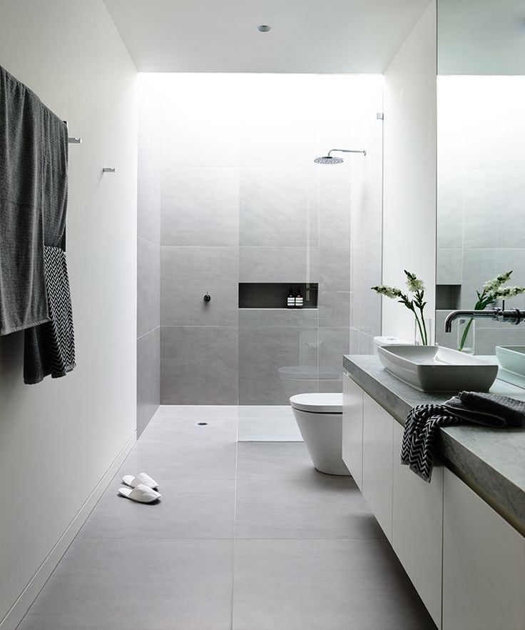 a minimalist grey and white bathroom with large scale tiles, a long vanity with a concrete countertop and a skylight over the shower