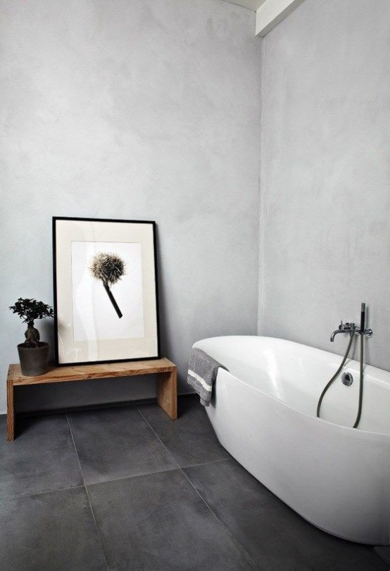 a minimalist bathroom with light grey walls, a graphite grey floor, white appliances and statement artworks