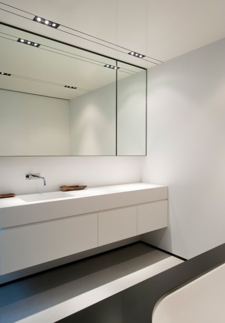 a sleek minimalist black and white bathroom with a statement mirror, a white floating vanity, a white bathtub and built-in lights