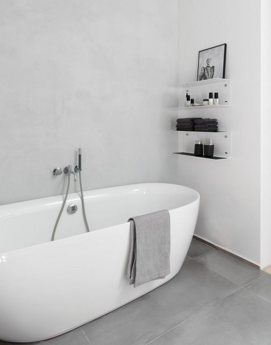 a white minimalist bathroom with a white tub, some wall shelves and a grey concrete floor