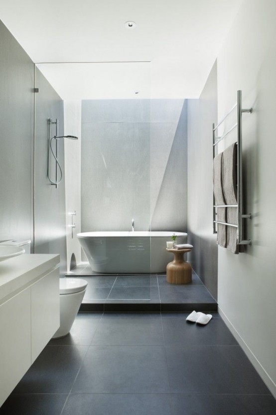a contrasting minimalist bathroom with sleek white walls, black tiles on the floor, a floating vanity and white appliances