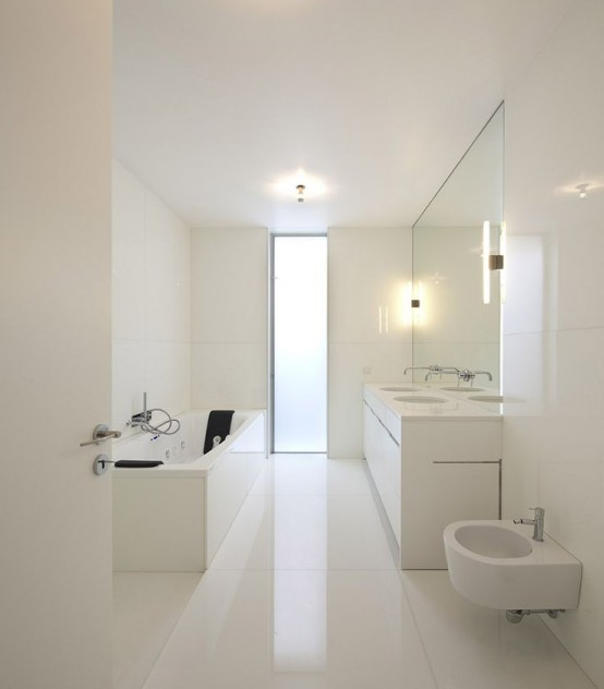 a white minimalist bathroom with large scale white tiles all over, a long double vanity and white appliances plus a vertical window with frosted glass